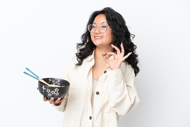 Giovane donna asiatica isolata su sfondo bianco che mostra segno ok con le dita mentre tiene in mano una ciotola di pasta con le bacchette