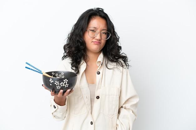 Giovane donna asiatica isolata su sfondo bianco con espressione triste mentre tiene in mano una ciotola di pasta con le bacchette