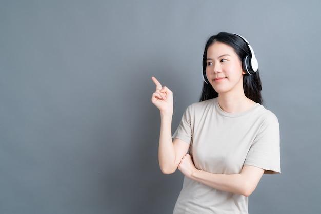Giovane donna asiatica che ascolta e si gode la musica con le cuffie su sfondo grigio