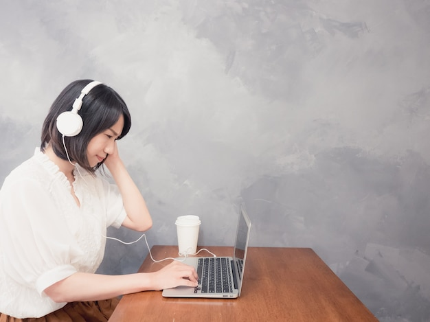 Giovane donna asiatica che ascolta le cuffie davanti al computer portatile
