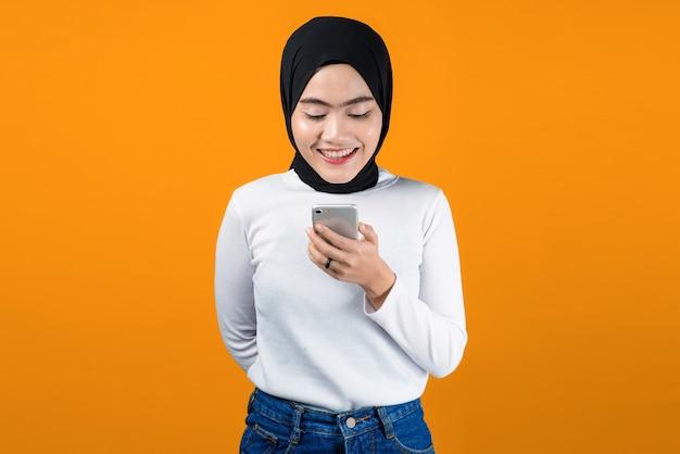 La giovane donna asiatica sembra felice usando il telefono cellulare