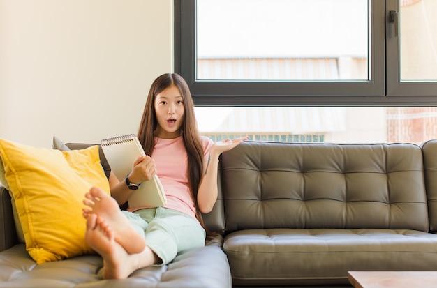 Giovane donna asiatica che sembra sorpresa e scioccata, con la mascella caduta tenendo un oggetto con una mano aperta sul lato