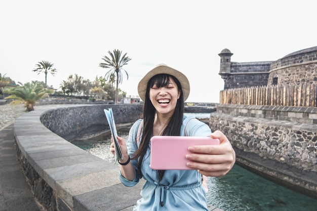 Giovane donna asiatica che fa video per vlog con la fotocamera dello smartphone
