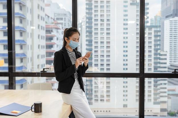 Responsabile della giovane donna asiatica che indossa la maschera per il viso utilizza lo smartphone durante la pausa pranzo in un ufficio moderno in centro