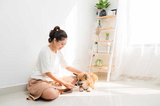 Giovane donna asiatica che gioca con il suo cane a casa