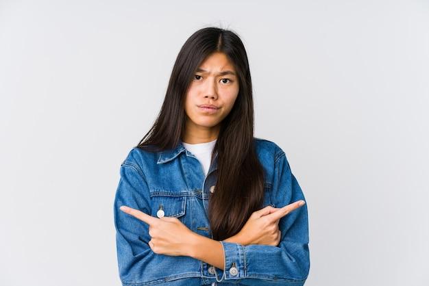 La giovane donna asiatica indica lateralmente, sta cercando di scegliere tra due opzioni.