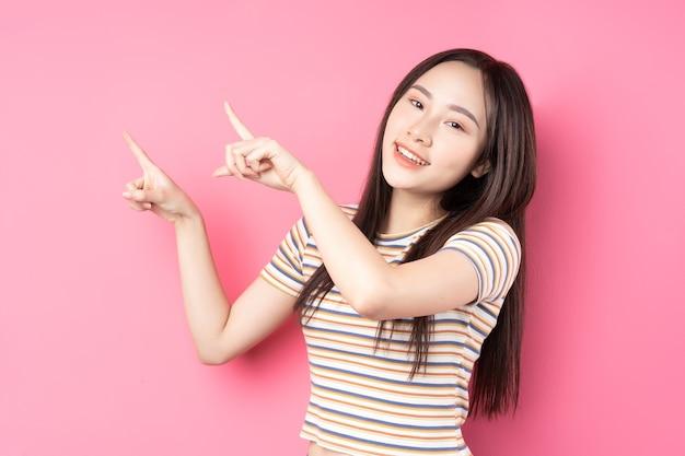 Giovane donna asiatica in posa sul rosa