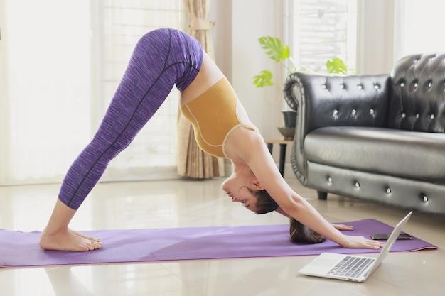 Giovane donna asiatica che pratica lezione di yoga con un gruppo di persone a casa in videoconferenza.
