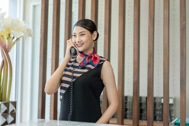 Receptionist di giovane donna asiatica che sorride e parla di benvenuto al telefono con i clienti dell'hotel