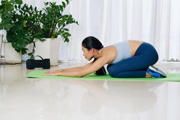 Giovane donna asiatica che si rilassa in balasana o posa per bambini sul tappetino da yoga a casa dopo l'allenamento