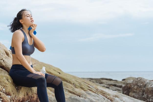 Giovane corridore asiatico della donna che riposa dopo l'allenamento che corre sulla spiaggia
