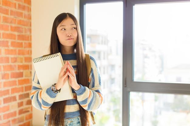 Giovane donna asiatica che complotta e complotta, pensa a trucchi e inganni subdoli, astuzia e tradimento