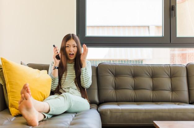 Giovane donna asiatica che grida con le mani in alto, sentendosi furiosa, frustrata, stressata e sconvolta