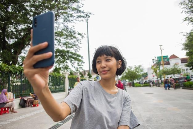 Selfie della giovane donna asiatica con il telefono cellulare negli spazi pubblici
