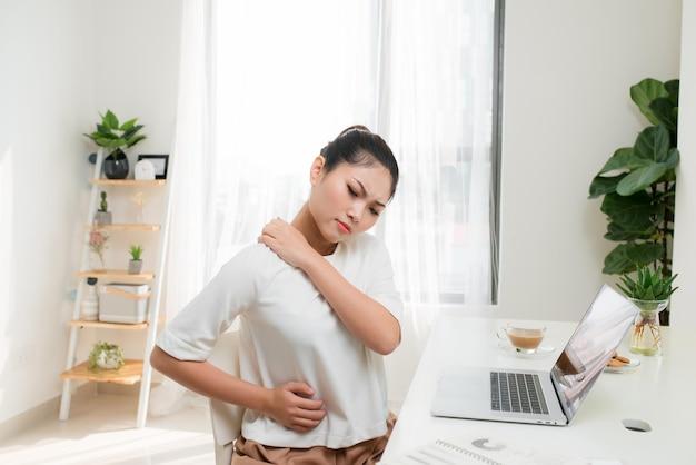 Concetto di dolore alla spalla della giovane donna asiatica alla sindrome dell'ufficio
