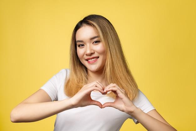 Segno della mano del cuore di manifestazione della giovane donna asiatica