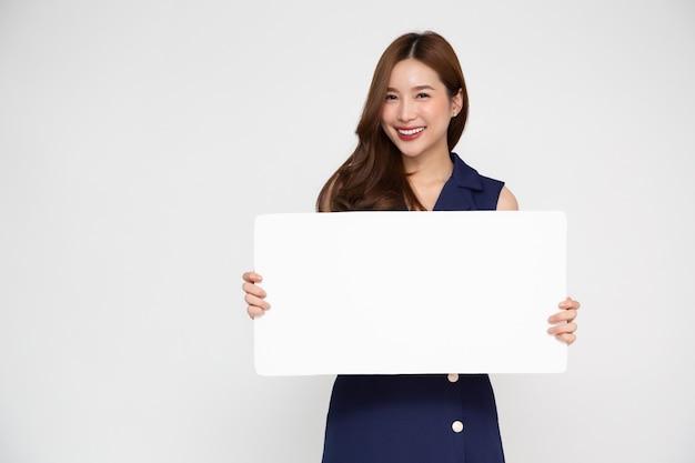 Giovane donna asiatica che mostra e che tiene tabellone per le affissioni bianco in bianco