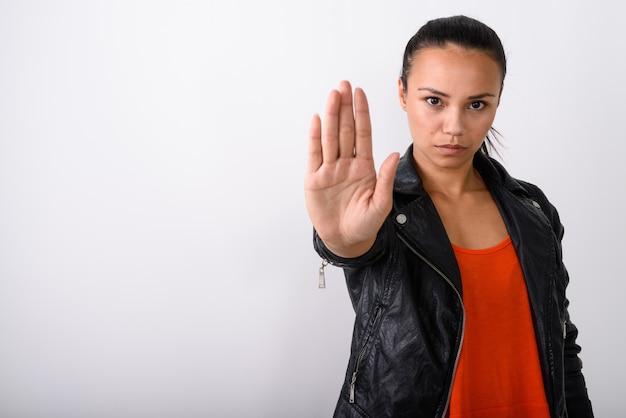 Giovane donna asiatica che mostra il segnale di stop mano mentre indossa giacca di pelle contro uno spazio bianco