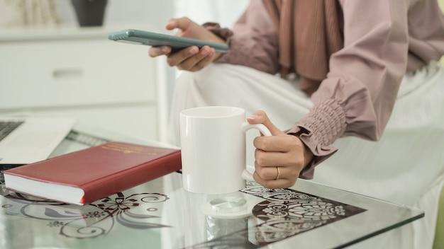 Giovane donna asiatica seduta a godersi un drink dopo il lavoro da casa