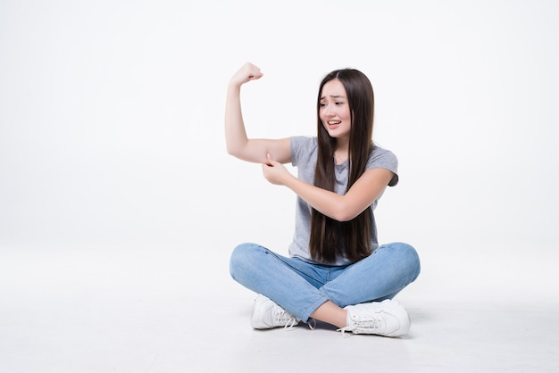Giovane donna asiatica che si siede sul pavimento sentendosi felice, soddisfatta e potente, flettendo in forma e bicipite muscoloso isolato sul muro bianco
