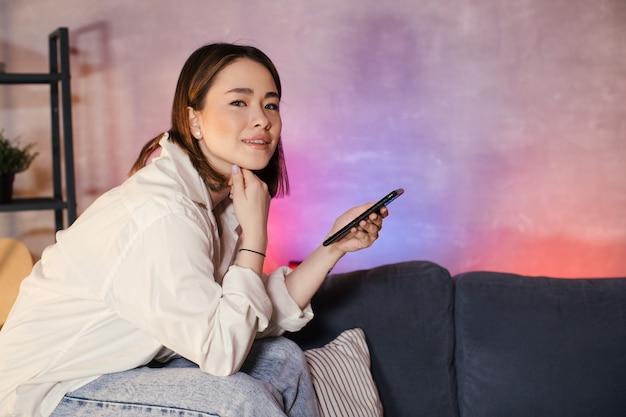La giovane donna asiatica che si siede su un divano in una stanza accogliente guarda la telecamera