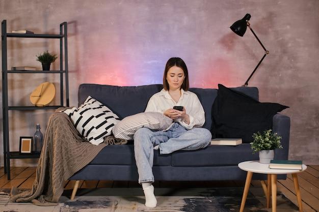 La giovane donna asiatica che si siede su un divano in una stanza accogliente guarda il telefono