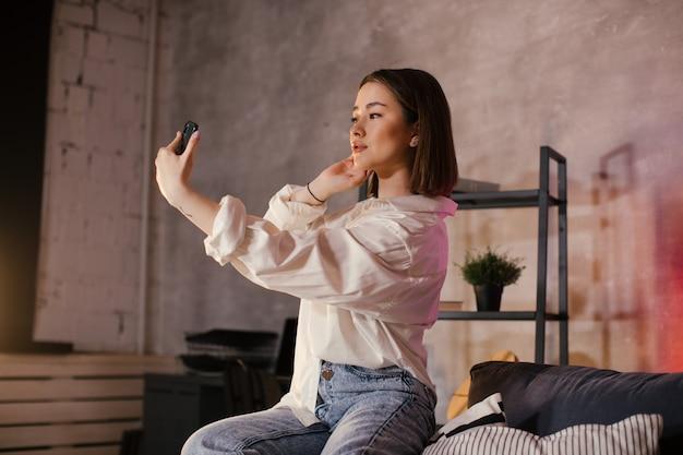 La giovane donna asiatica che si siede su un divano in una stanza accogliente prende un selfie e sorride