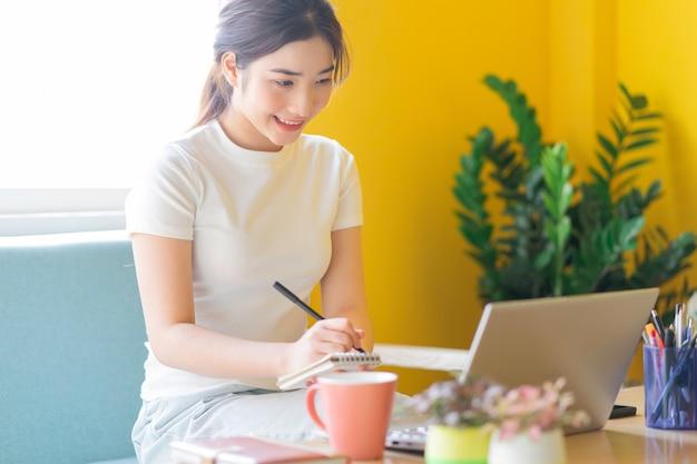 Giovane donna asiatica che si siede sul divano che lavora a casa