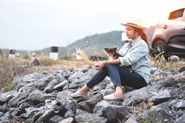 Giovane donna asiatica che si siede con i cani della chihuahua con l'automobile nera di eco della berlina.