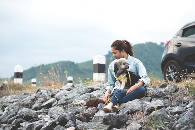 Giovane donna asiatica che si siede con i suoi cani al lato della strada con l'automobile nera e la pietra del miglio.