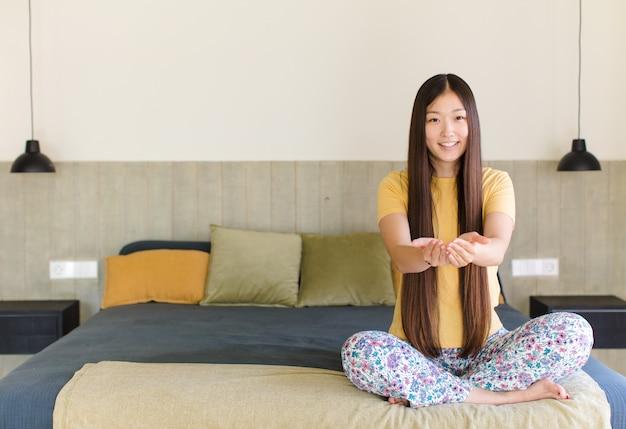Giovane donna asiatica sorridente, sentendosi felice, positiva e soddisfatta