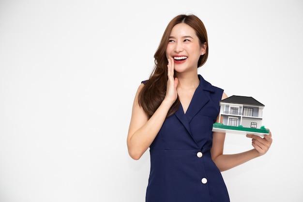 Giovane donna asiatica che sorride e che tiene il modello del campione della casa