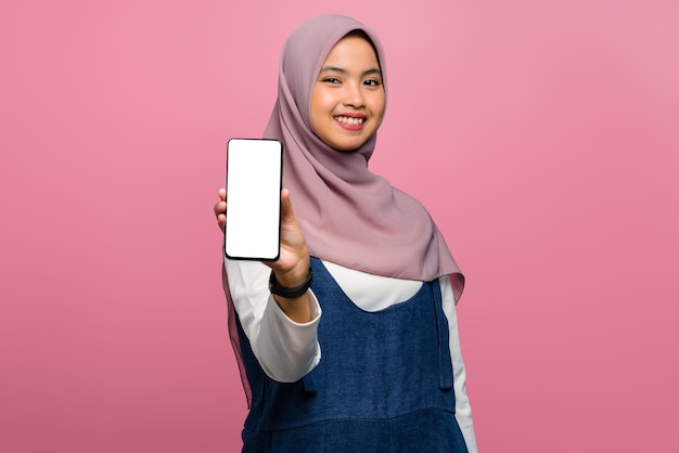 Giovane donna asiatica che sorride e che tiene smartphone