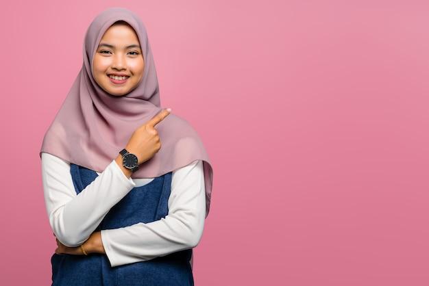 Giovane donna asiatica che sorride e che indica al lato