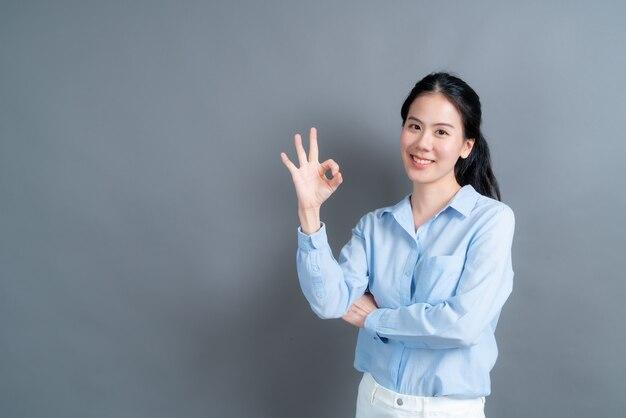 Giovane donna asiatica che sorride e che mostra segno giusto