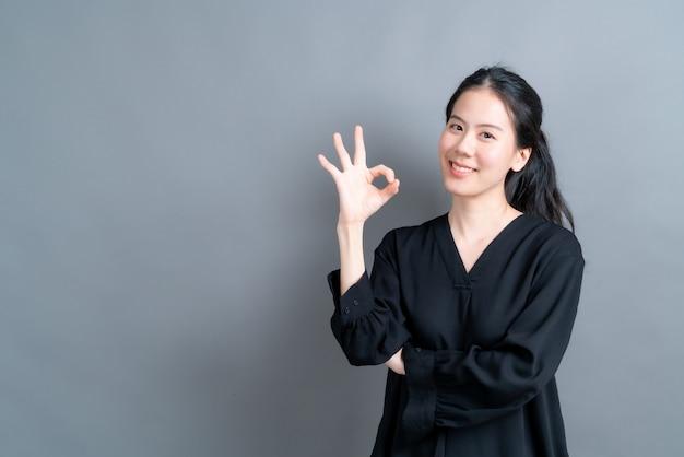 Giovane donna asiatica che sorride e mostra il segno ok