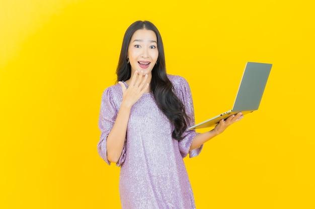 Giovane donna asiatica che sorride con il computer portatile?