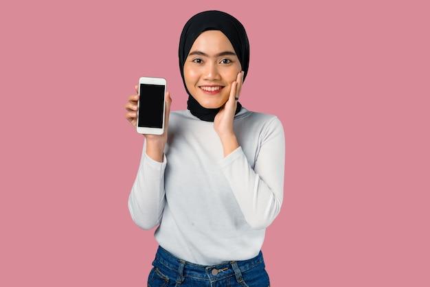 Giovane donna asiatica che sorride con l'espressione felice e che tiene il telefono cellulare