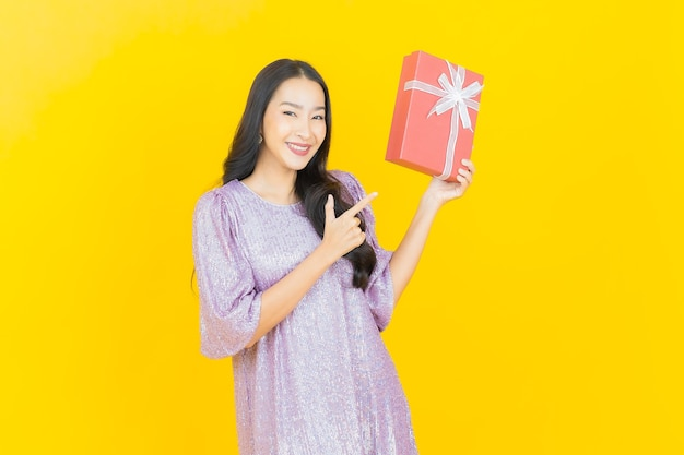 Giovane donna asiatica sorridente con confezione regalo rossa su giallo
