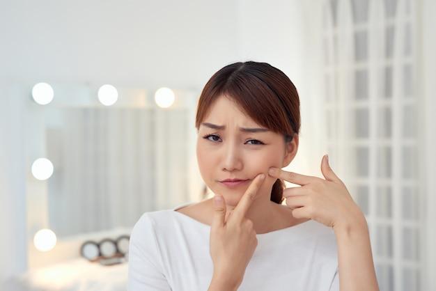 La giovane donna asiatica le stringe l'acne