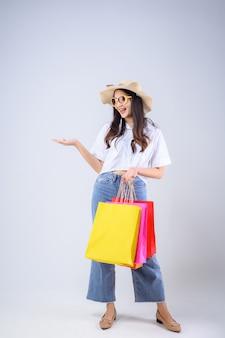 Giovane donna asiatica stare in possesso di una borsa della spesa multicolore e stese la mano con una faccia felice su sfondo bianco.