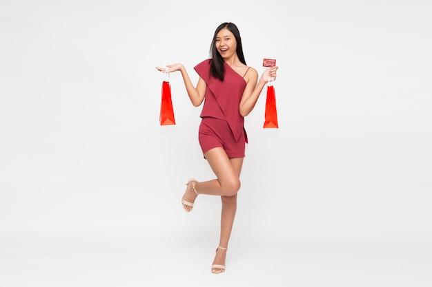 Giovane donna asiatica in piedi e con in mano le borse della spesa isolate su sfondo bianco