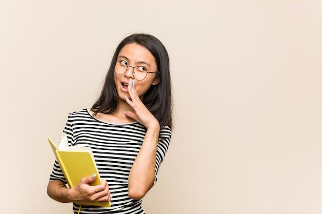 Giovane studentessa asiatica che tiene un libro