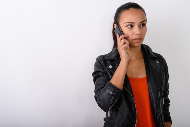 Giovane donna asiatica parlando al telefono cellulare mentre indossa giacca di pelle contro uno spazio bianco