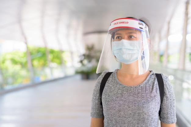 Giovane donna asiatica che pensa con maschera e schermo facciale per la protezione dallo scoppio del virus corona in città