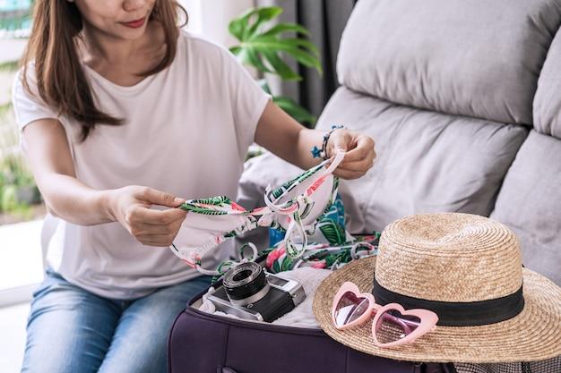 Viaggiatore della giovane donna asiatica che prepara la sua valigia e che pianifica per le vacanze estive