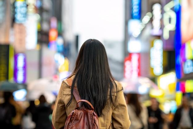 Giovane viaggiatore asiatico della donna che viaggia e che compera in via di myeongdong