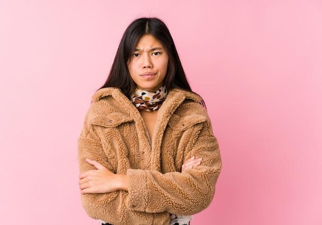 Sguardo infelice della giovane donna asiatica a porte chiuse con l'espressione sarcastica.