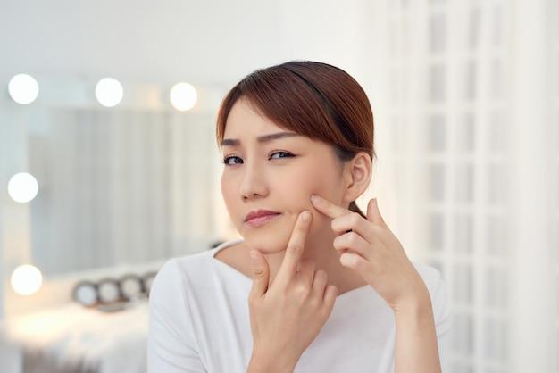 La giovane donna asiatica infelice tocca la sua pelle