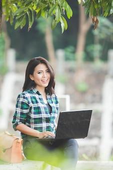 Giovane donna asiatica che per mezzo del computer portatile mentre sedendosi sul parco